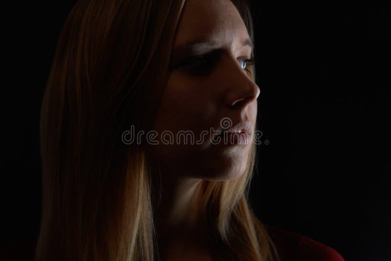 La jeune femme blonde songeuse regarde au côté photographie stock libre de droits