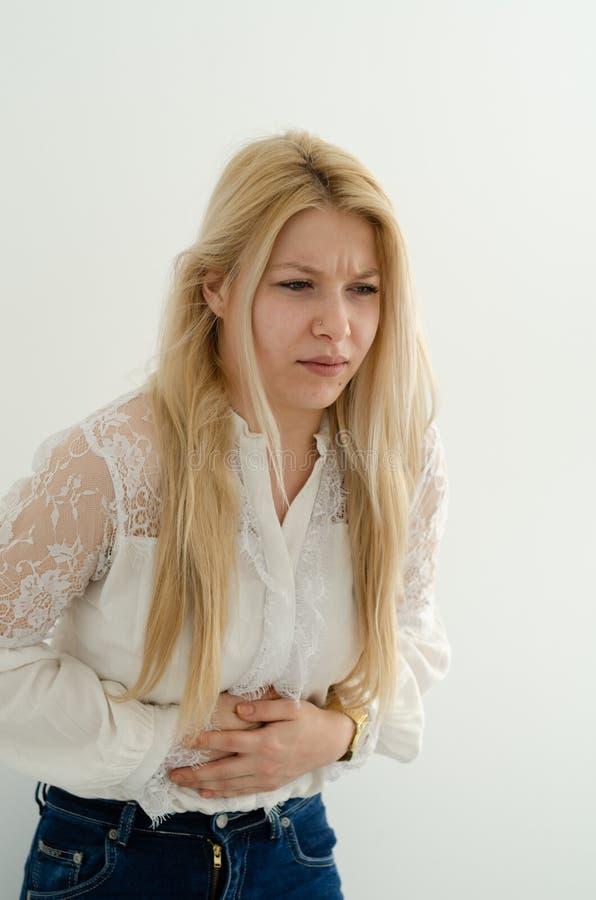La jeune femme blonde souffre de la douleur abdominale images libres de droits