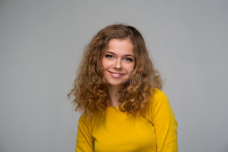 La jeune femme bouclée dans des vêtements jaunes a contrarié regarder les cheveux o image stock
