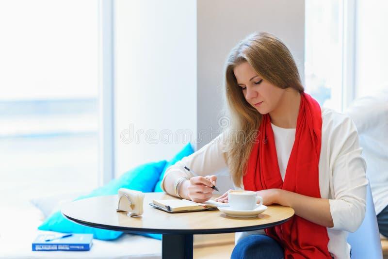 La jeune femme caucasienne écrit une certaine idée ou lettre dans son carnet, par le stylo photos libres de droits