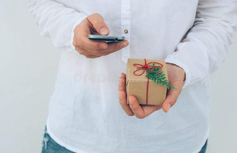 La jeune femme caucasienne dans la chemise de jeans se tient dans le boîte-cadeau de mains enveloppé en papier brun de métier att images libres de droits