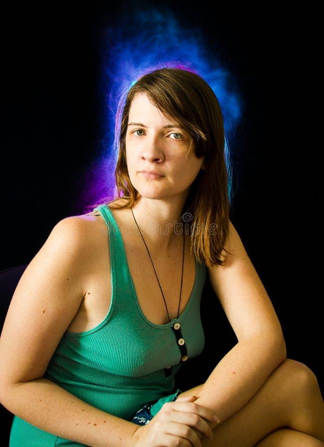 La jeune femme caucasienne dans la robe verte avec les cheveux pourpres et bleus s'allume sur le fond noir image stock