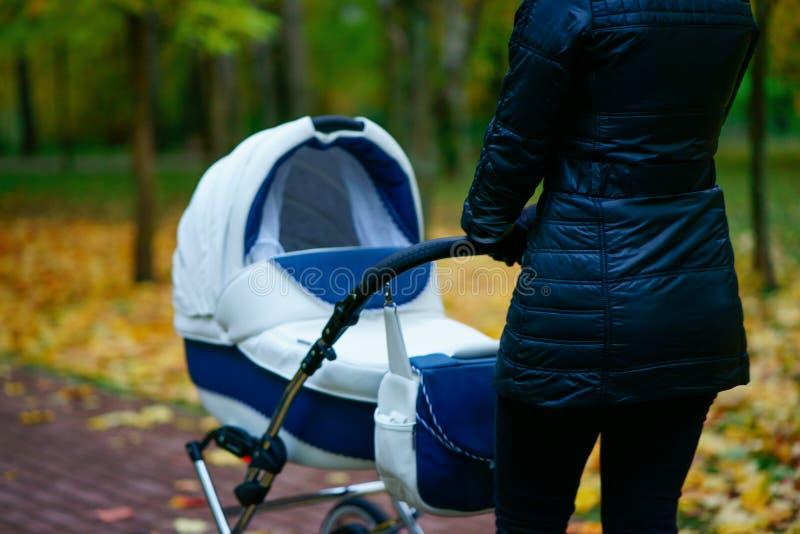 La jeune femme caucasienne pousse la voiture d'enfant blanche tandis qu'elle marchant au parc d'automne avec de belles feuilles j photo stock