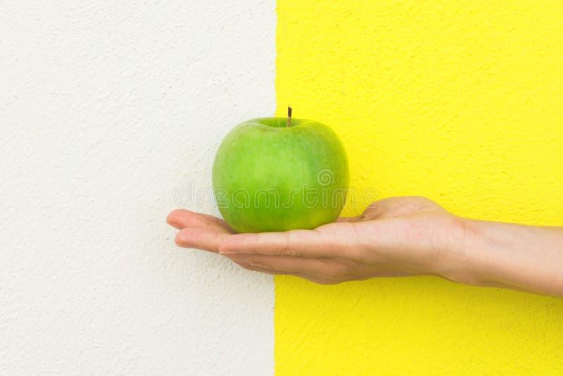 La jeune femme caucasienne tient à disposition la pomme organique verte sur le mur peint blanc jaune de duotone Vegan en bonne sa images libres de droits
