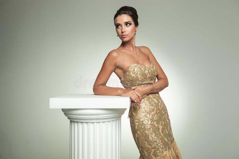 La jeune femme chique dans la longue robe élégante se penche sur la colonne image stock
