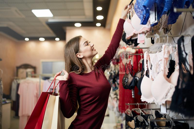 La jeune femme choisit le soutien-gorge sexy parmi l'ensemble dans une boutique La jolie fille considère le soutien-gorge avec de photos stock
