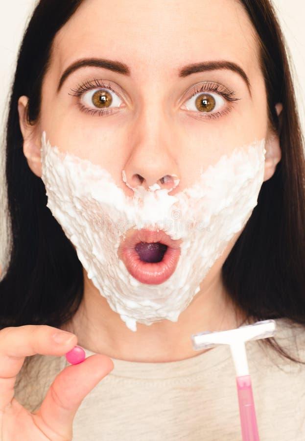La jeune femme choquée avec raser la mousse sur son visage tient une pilule et un rasoir Concept des problèmes hormonaux photo stock