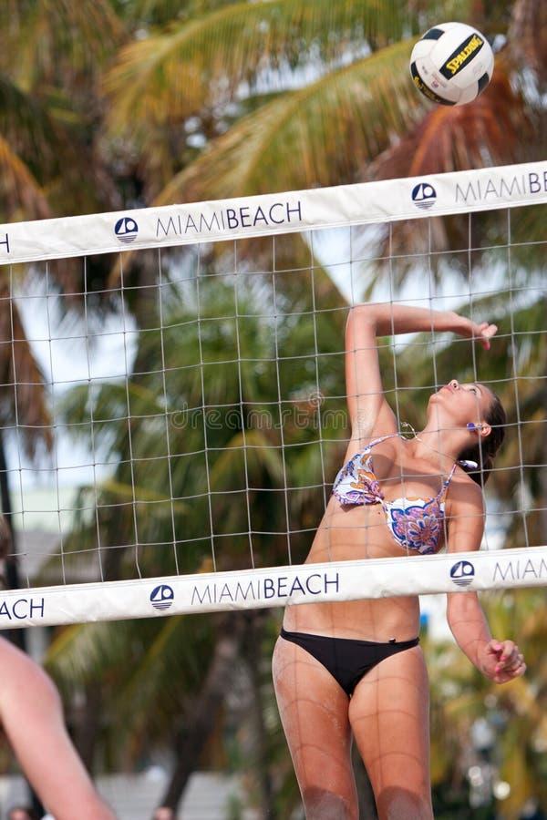 La jeune femme cloue la boule dans le match de volley de Miami Beach image stock