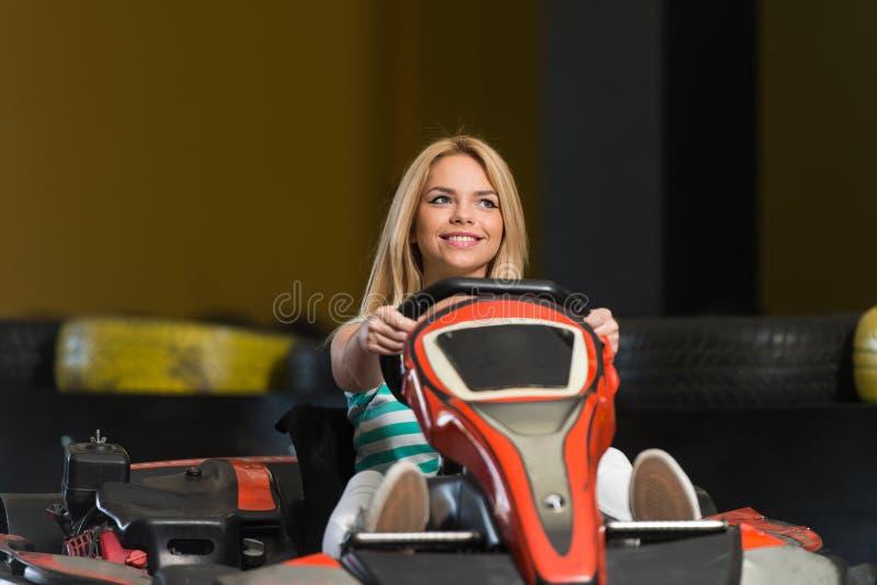 La jeune femme conduit la voiture de kart image libre de droits