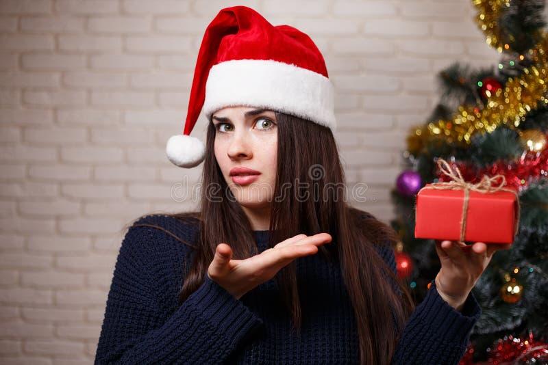 La jeune femme contrariée mignonne dans le chapeau de Santa est déçue par He image stock