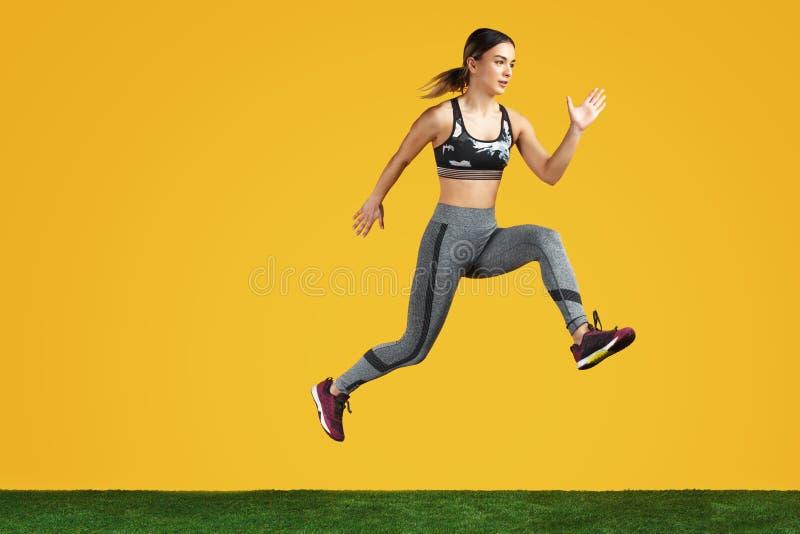 La jeune femme convenable étonnante de photo font l'exercice sur l'herbe verte au-dessus du fond jaune images stock