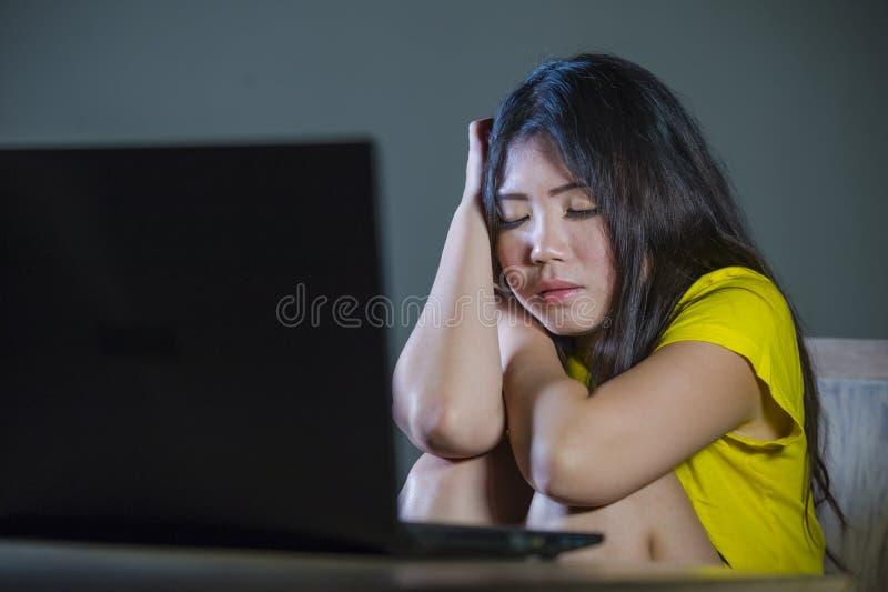 La jeune femme coréenne asiatique assez choquée et étonnée regardant soumise à une contrainte le sentiment d'ordinateur portable  image libre de droits