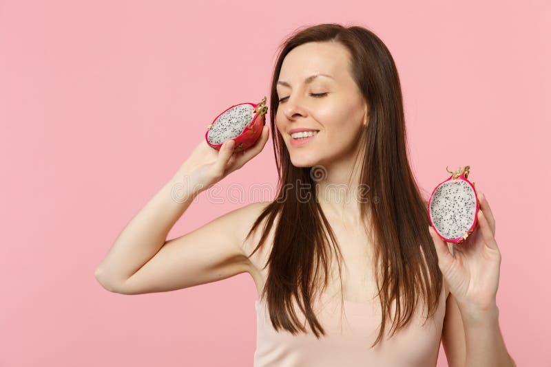 La jeune femme décontractée gardant des yeux a clôturé tenir le pitahaya mûr frais, fruit du dragon d'isolement sur le mur en pas photos libres de droits