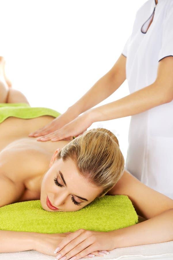 La jeune femme décontractée se trouvant sur une table de massage et a le massage photos libres de droits