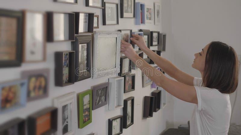 La jeune femme décore les murs de son salon photos stock