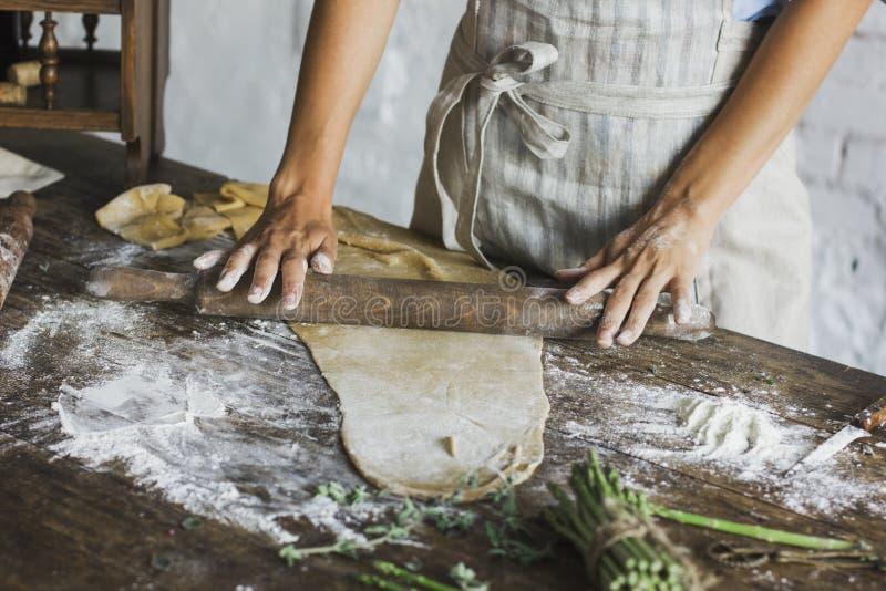 La jeune femme déroule la pâte avec la goupille photographie stock