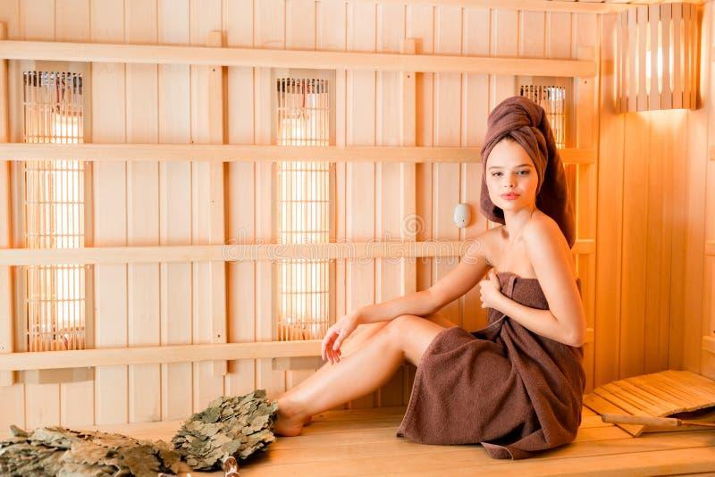 La jeune femme détendant dans un sauna s'est habillée dans une serviette Intérieur du nouveau sauna finlandais, panneaux infrarou image libre de droits