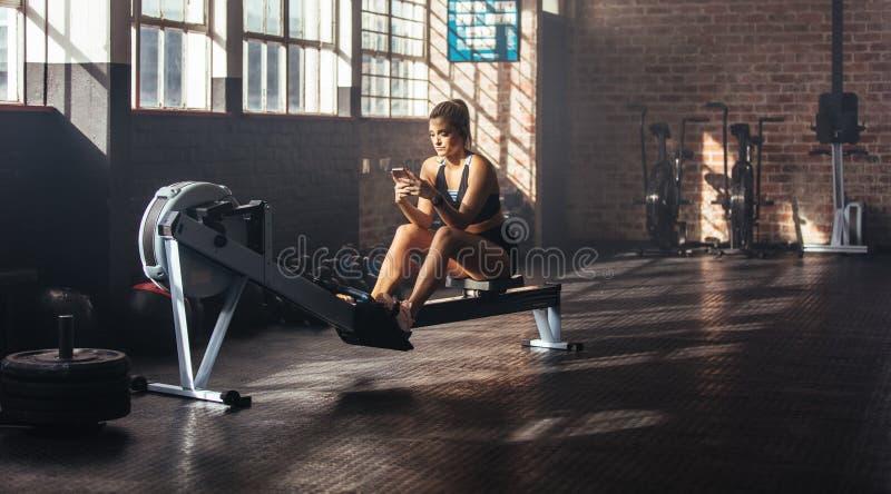 La jeune femme détendant pendant établissent au gymnase images stock