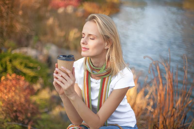 La jeune femme détendent et appréciant buvant du café sur le fond naturel d'air frais de matin photo stock