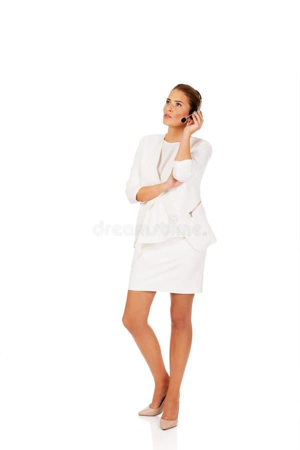 La jeune femme d'affaires écoutent quelqu'un aux écouteurs photographie stock libre de droits