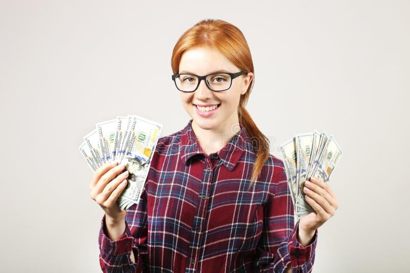 La jeune femme d'affaires attirante posant avec le groupe d'USD encaissent dedans des mains montrant des émotions positives et l' image libre de droits