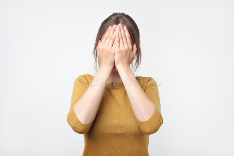 La jeune femme d'affaires cache son visage, photo de studio sur un fond gris photo stock