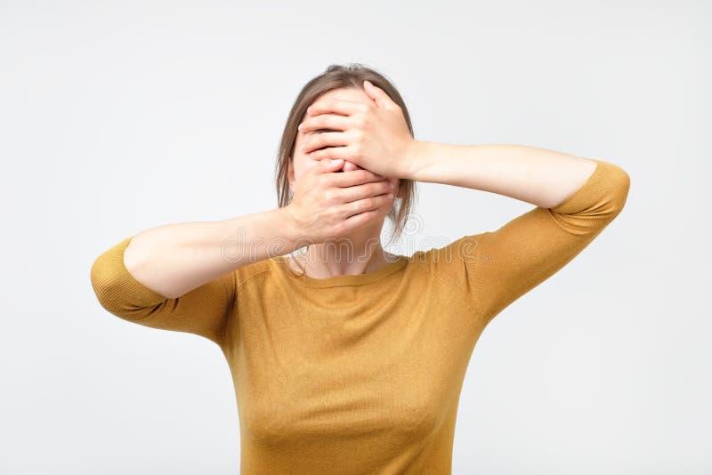 La jeune femme d'affaires cache son visage, photo de studio sur un fond gris image libre de droits