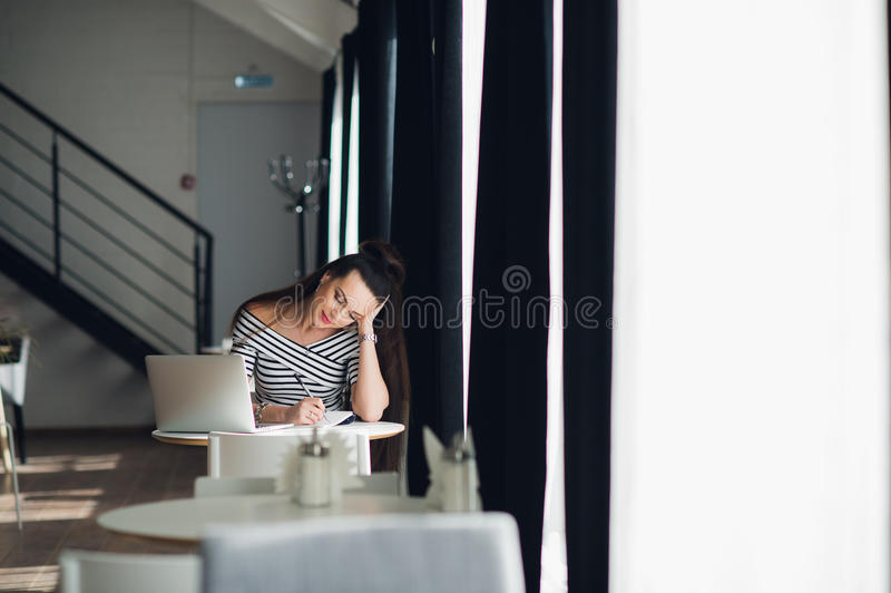 La jeune femme d'affaires dans des vêtements à la mode est principale conversation d'affaires sur les notes de téléphone et d'écr images libres de droits