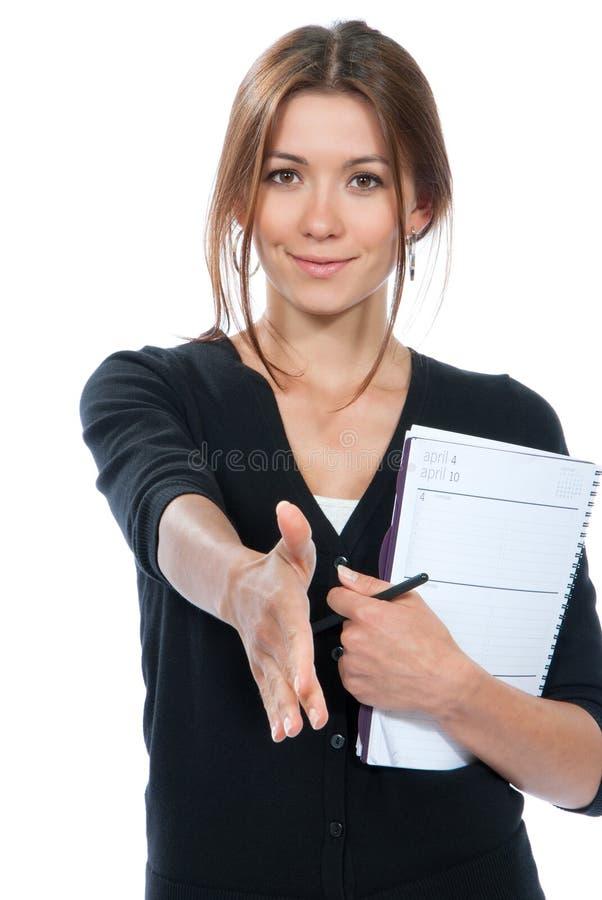 La jeune femme d'affaires de brune donnent la poignée de main et le sourire images stock