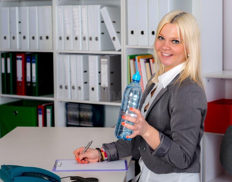 La jeune femme d'affaires est eau potable  image stock