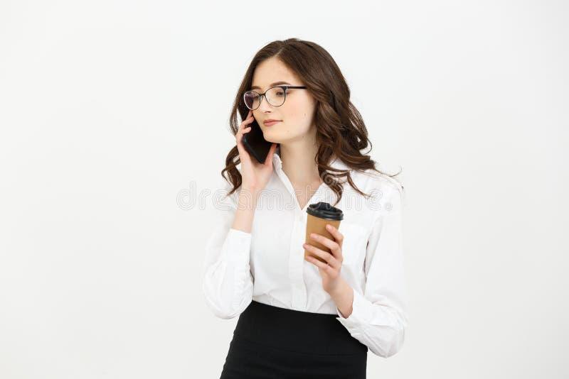 La jeune femme d'affaires moderne attirante parlant au téléphone portable et se tenant emportent la tasse de café dans le bureau  photo stock