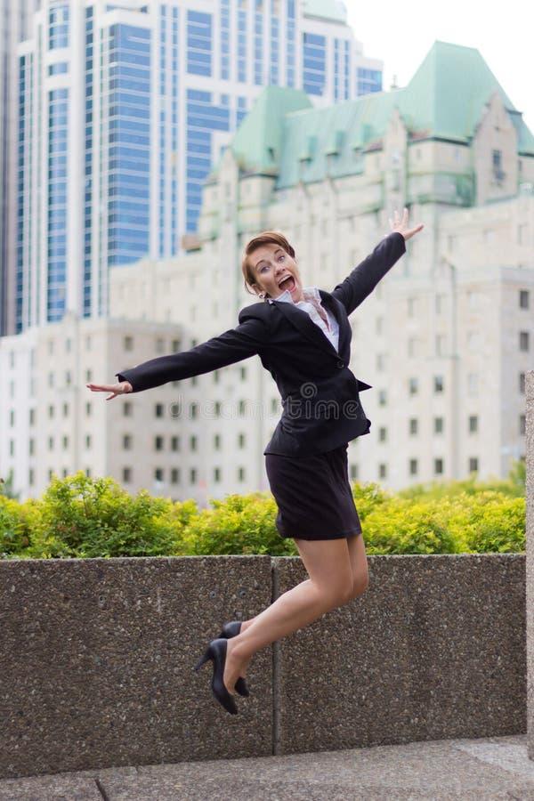La jeune femme d'affaires saute pour la joie avec le fond de ville photographie stock