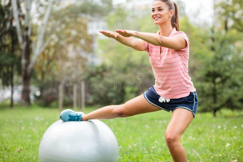 La jeune femme d'ajustement faisant des postures accroupies avec une jambe se reposant sur une boule de forme physique, bras s'es photo libre de droits