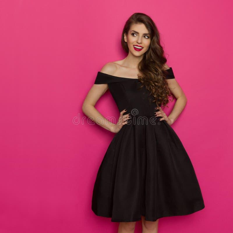 La jeune femme d'Elegany dans la robe de cocktail noire regarde loin images stock