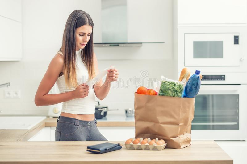 La jeune femme dans la cuisine à la maison vérifie la facture Achat sur une table dans un sac de papier images stock