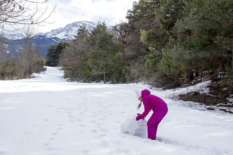 La jeune femme dans des vêtements lumineux d'hiver fait un bonhomme de neige dans la forêt photos libres de droits