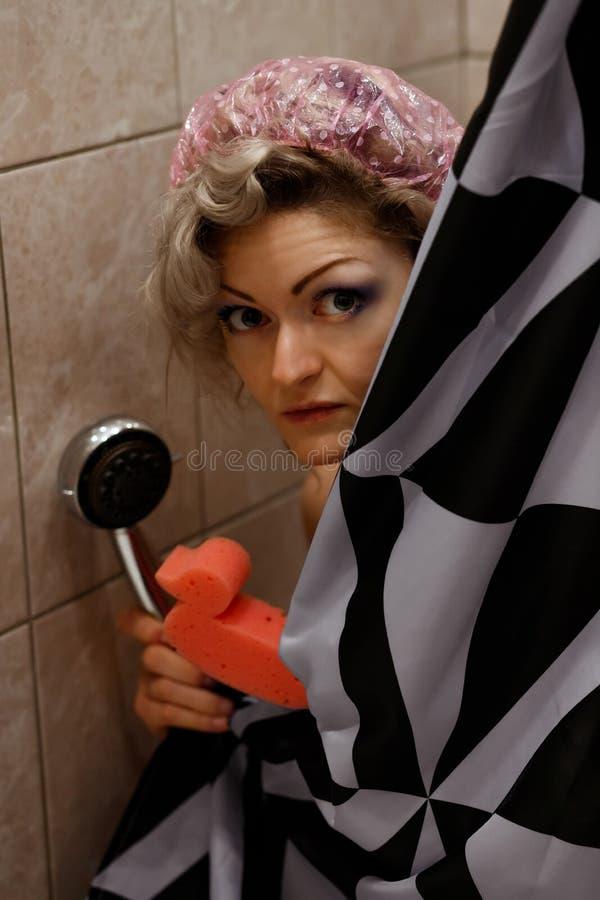 La jeune femme dans la douche couverte de rideau en douche utilise un chapeau de douche rose et tient une éponge en forme de cana images libres de droits