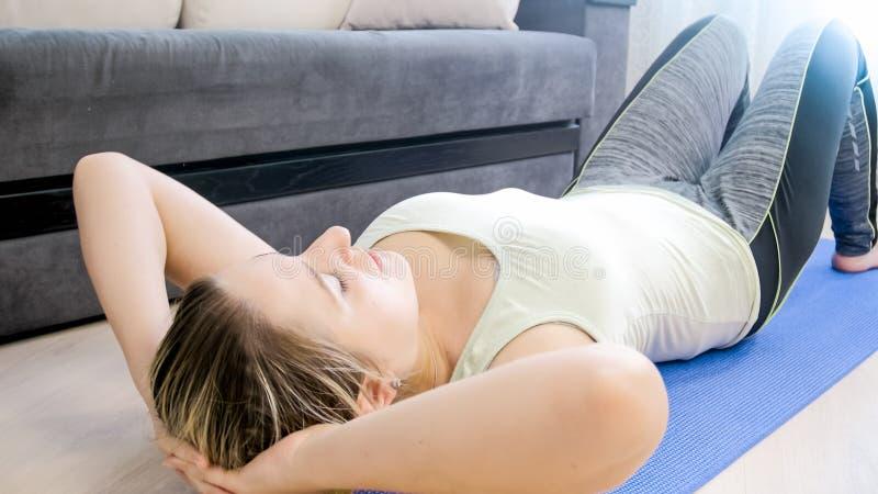 La jeune femme dans la forme physique vêtx le mensonge sur le tapis au salon photos stock