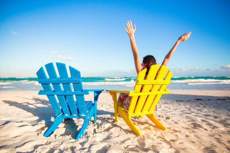 La jeune femme dans la chaise de plage a soulevé ses mains  photographie stock libre de droits