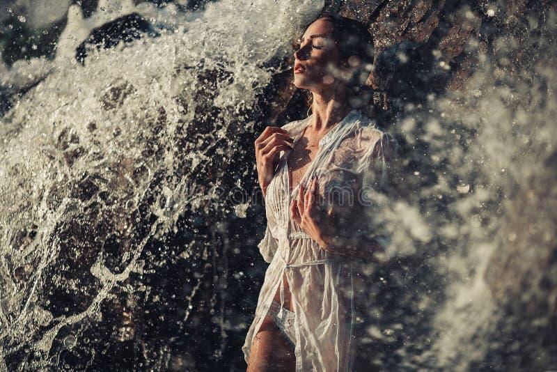 La jeune femme dans la chemise et le bikini blancs se tient dans les écoulements d'eau près image stock