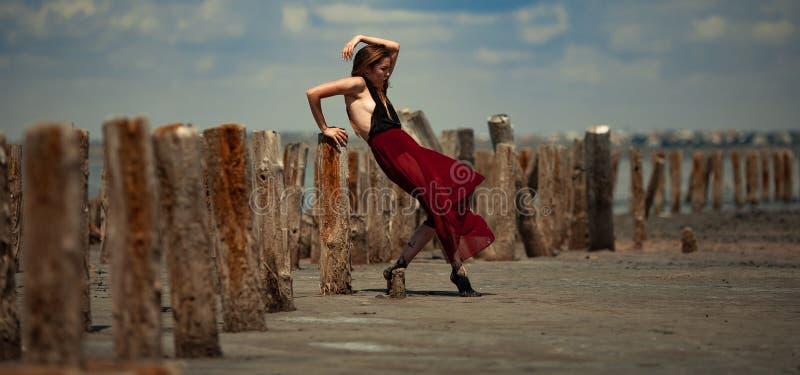 La jeune femme dans la longue robe danse en sable sur le fond de plage photo stock