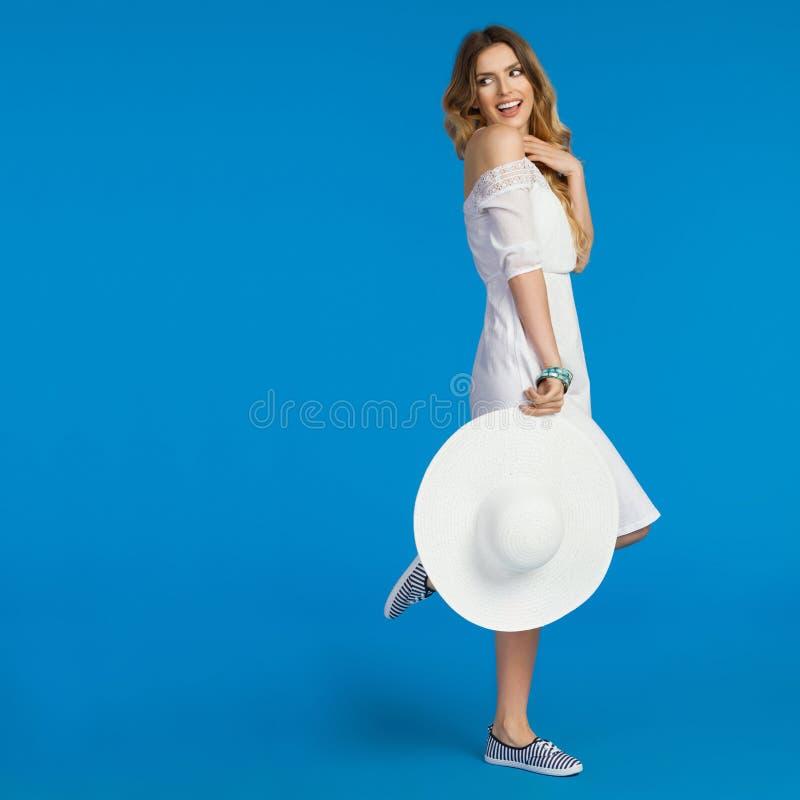 La jeune femme dans la robe blanche d'été regarde au-dessus du Sholuder photos libres de droits