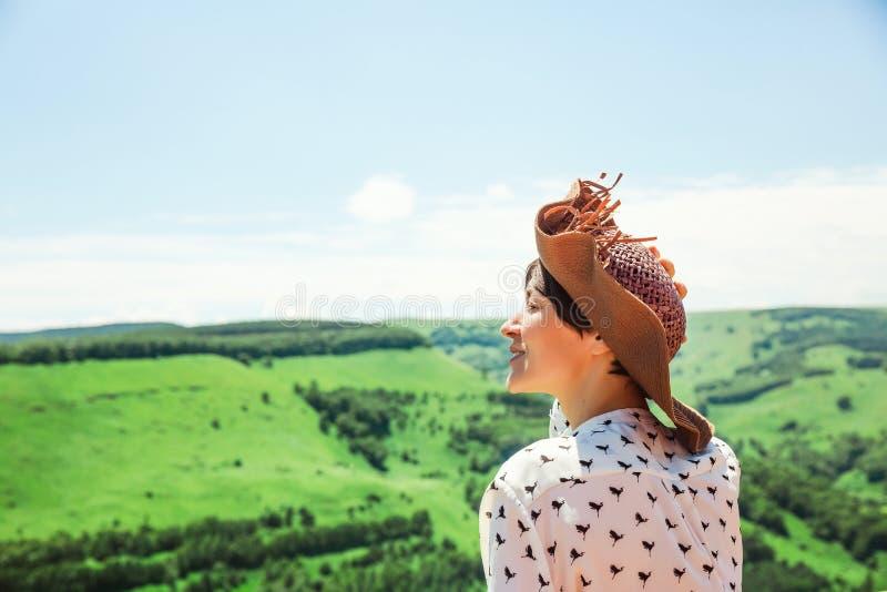 La jeune femme dans le chapeau appréciant des montagnes aménagent des vacances en parc actives extérieures d'émotions de mode de  images libres de droits
