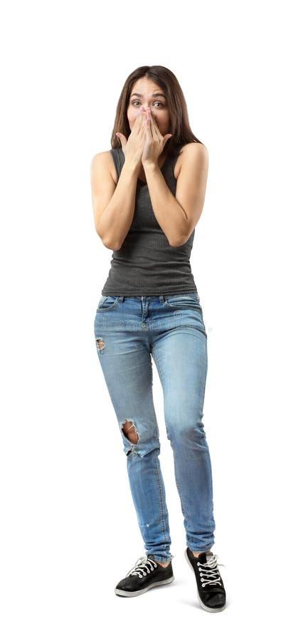 La jeune femme dans le dessus gris et des blues-jean couvrant la bouche et le nez de ses mains, poids sur le pied droit, genou ga images libres de droits