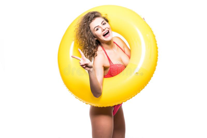 La jeune femme dans le maillot de bain avec un anneau gonflable et la main montrant la victoire font des gestes d'isolement au-de photographie stock libre de droits
