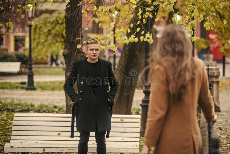 La jeune femme dans le manteau de chameau va chez l'ami en parc image stock