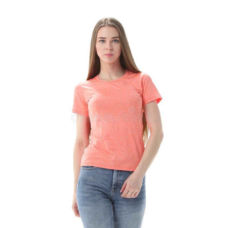 La jeune femme dans les jeans et le T-shirt va en avant D'isolement sur le blanc photo stock