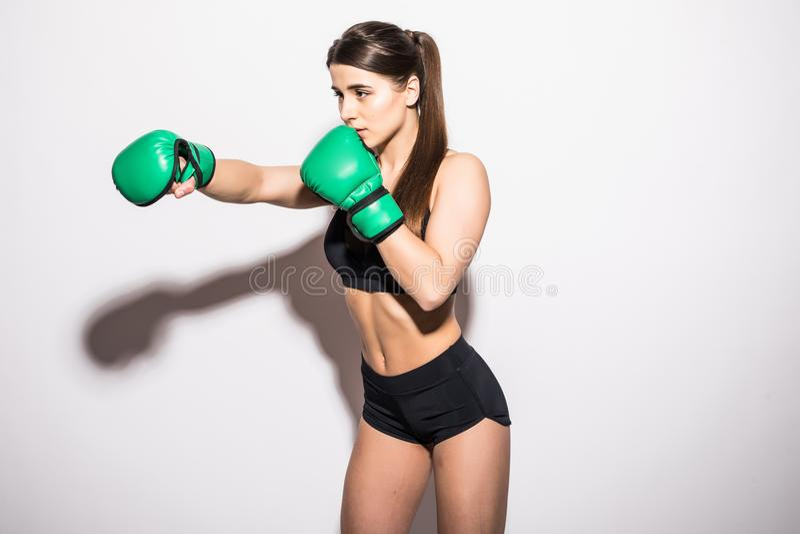 La jeune femme dans les vêtements de sport et les gants de boxe verts sourit sur un fond d'isolement par blanc photos stock