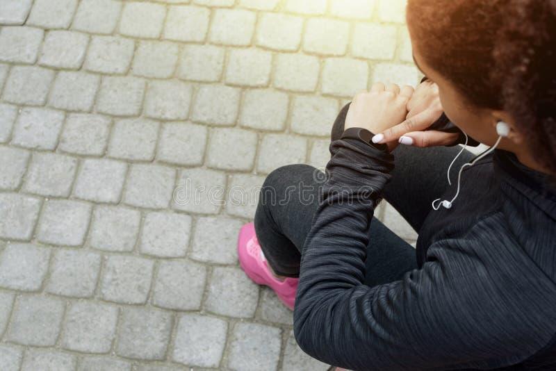 La jeune femme dans les vêtements de sport vérifie le traqueur de forme physique photographie stock libre de droits