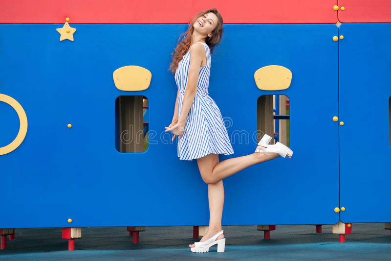 La jeune femme de brune dans la lumière a barré la robe bleue blanche ayant l'amusement au terrain de jeu extérieur photos stock